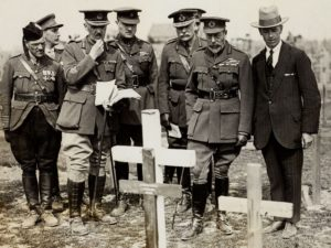 Group of men, some in uniform, looking at rows of wooden crosses